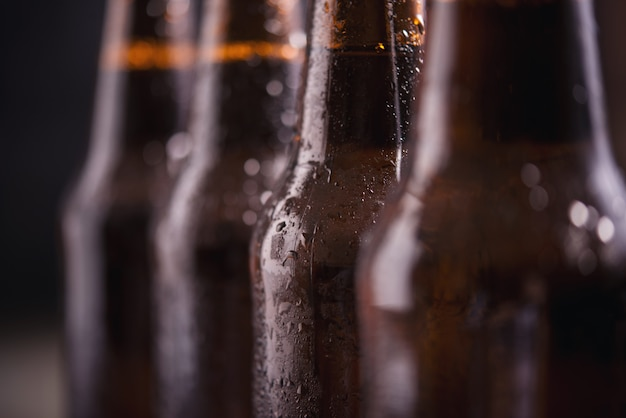 Close up glass bottles of beer with ice on dark background