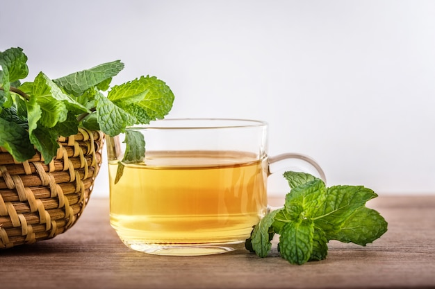 Close up a glass cup of mint tea with green fresh peppermint leaves Premium Photo