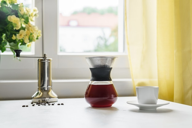 Close up of glass filter coffee maker at the kitchen in front of the window. making filtering espresso at home. autumn concept