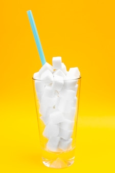 Close up of glass full of sugar cubes over yellow