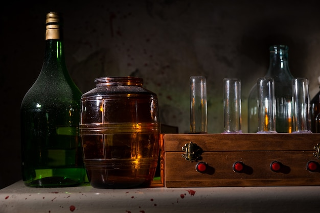 Close up of glass jars and bottles with blood spattered wall in a halloween horror concept