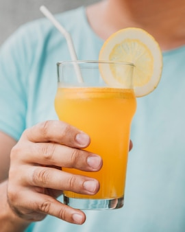 Close-up glass of natural orange juice held by hand