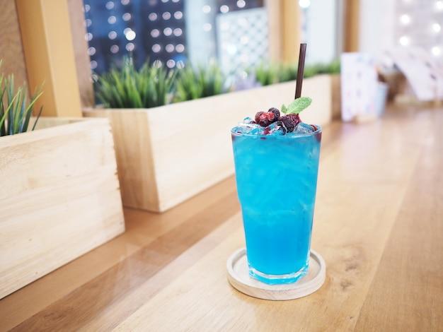저녁 식사 레스토랑에서 나무 테이블 위에 나무 접시에 베리 과일 토핑을 얹은 파란색 칵테일 한 잔을 닫습니다