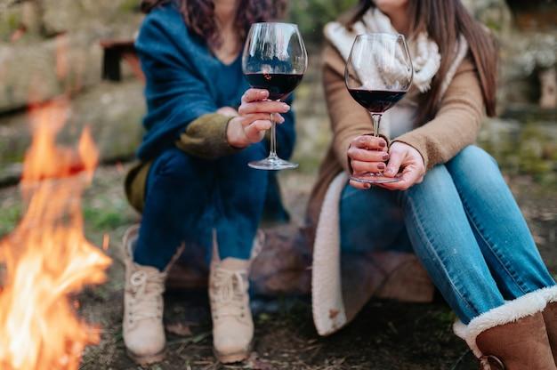모닥불 옆 배경에 인식 할 수없는 여자와 레드 와인의 근접 유리.