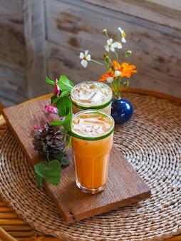 카페에서 나무 빈티지 테이블에 꽃 장식과 함께 태국 우유 차와 차가운 커피의 유리를 닫습니다.