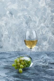 ダークブルーとライトブルーの大理石の背景にウイスキーのグラスと白ブドウのクローズアップグラス。垂直