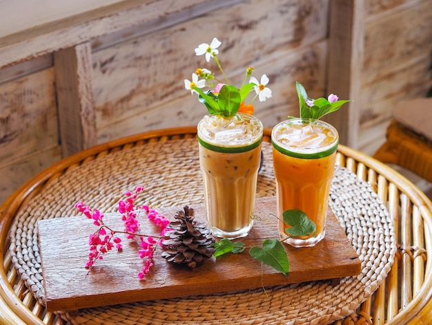 Close up glass of thai milk tea and cold coffee with flower decoration on wooden vintage table at cafe.
