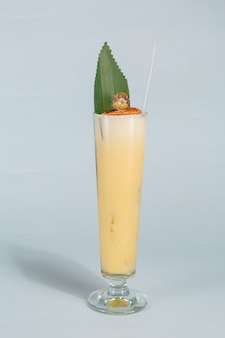 Close up of a glass of tropical pina colada cocktail on white  with copy space. summer time vacation concept.