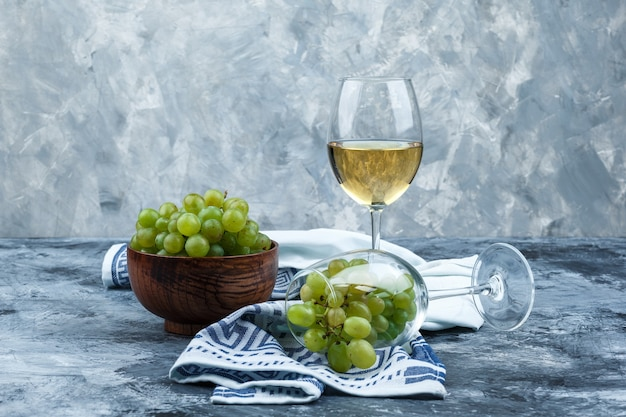 Close-up glass of white grapes with glass of whisky, bowl of grapes, kitchen towel on dark and light blue marble background. horizontal