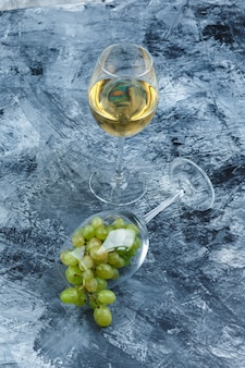 Close-up glass of white grapes with glass of whisky on dark blue marble background. vertical
