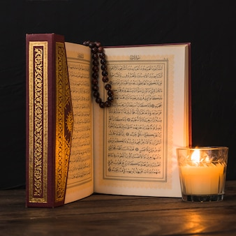 Close-up glass with candle and quran