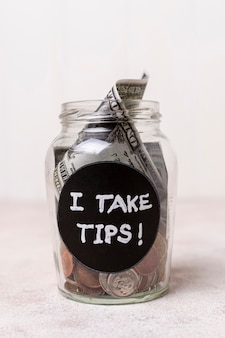 Close-up glass with money as tips