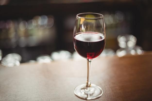 Primo piano di vetro con vino rosso sul tavolo