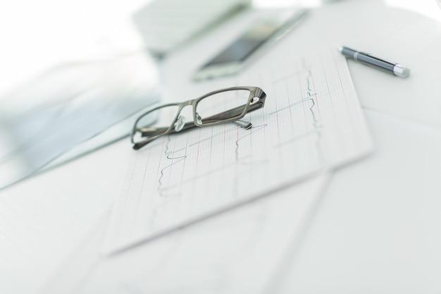 閉じる。セラピストの机の上の眼鏡とペン。コピースペースのある写真