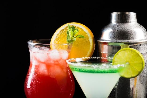 Close-up di bicchieri di cocktail con shaker e cubetti di ghiaccio