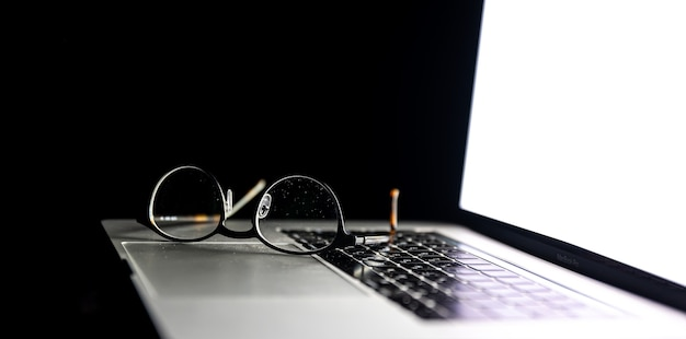 Close up of glasses on laptop in the dark