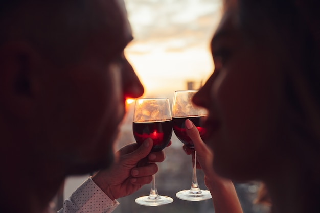 Close up of glasses with wine holding by lovers