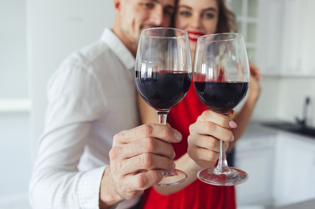 Close up of glasses with wine holding by pretty couple
