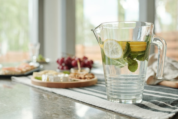Close-up of glassy pitcher of lemonade on stripped napkin prepared for dinner party at home