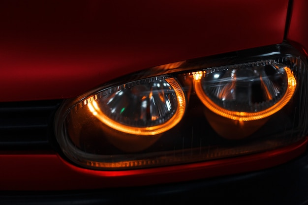 Close-up of a glowing led headlight and red car