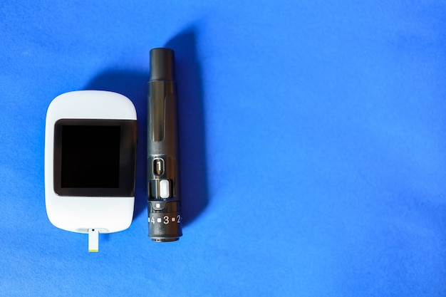 Close up of glucose meter with lancet on blue background