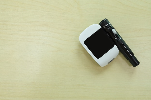 Close up of glucose meter with lancet on wooden table.