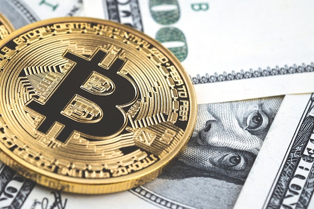 Close up gold bitcoin coins on one hundred us dollar bills background.