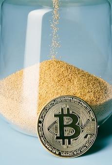 모래시계 앞에서 금 비트코인을 닫습니다. 암호화폐, 돈과 시간