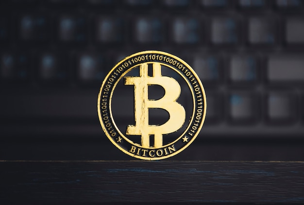 Close up of gold bitcoin on the wooden table with a blurred keyboard background