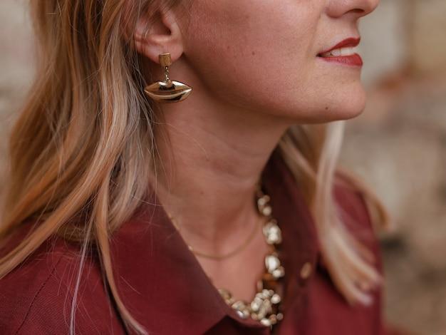 女の子の耳のクローズアップゴールドイヤリングと美しいネックレス
