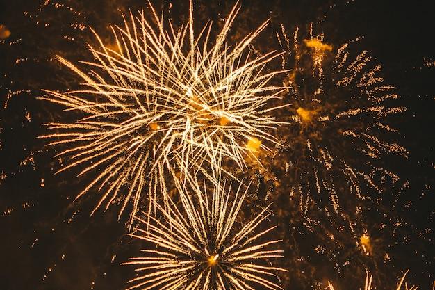 Крупным планом золотой праздничный фейерверк на черном