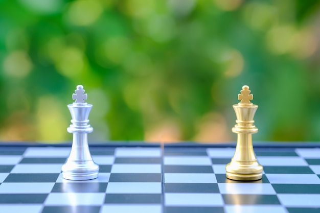 Close up of gold and silver king chess pieces on chessboard with green nature background