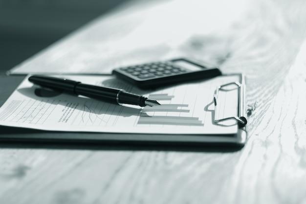 閉じる。テーブルの上の金の先端のペンと財務チャート。