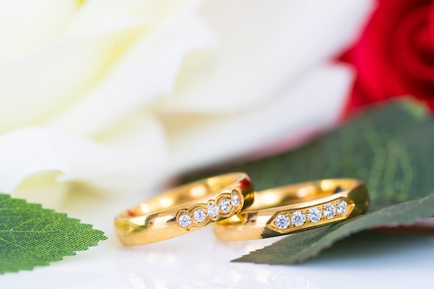 Close up of gold wedding rings and red rose