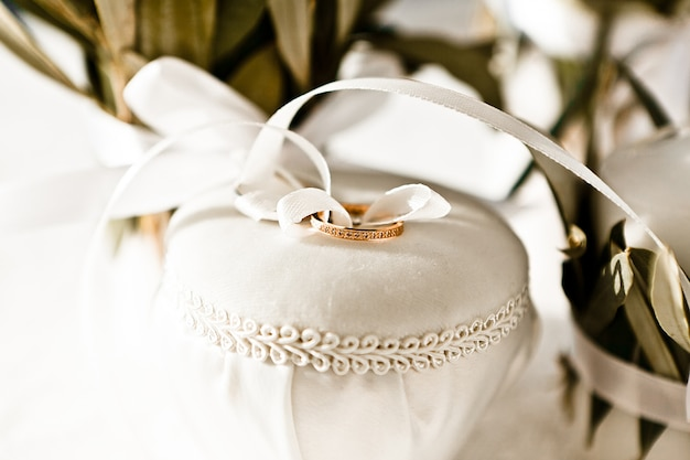 Close-up of gold wedding rings tied with a white silk ribbon to a jewelry box, selective focus