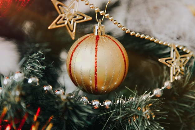 Close up of golden christmas ball on the pine tree branch with copyspace
