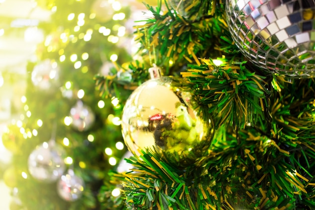Close up. a golden gift hang on chrismas tree. blurred background