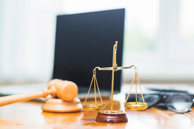 Close-up of golden justice scale on wooden desk in courtroom