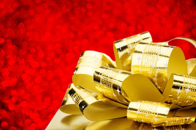 Close up golden present box with big bow at bokeh white blur background