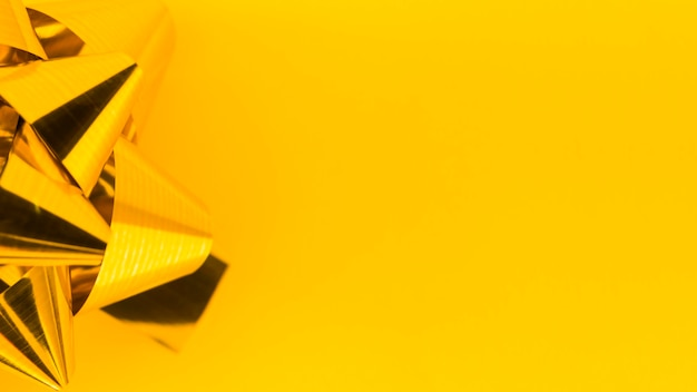 Close-up of golden ribbon bow on yellow backdrop