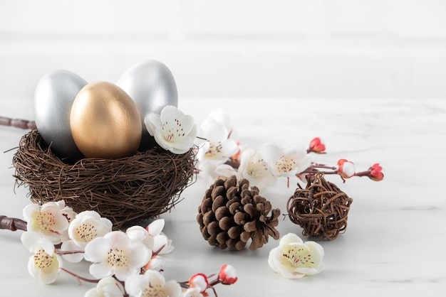 Close up of golden and silver easter eggs in the nest with white plum flower on bright white wooden table background.