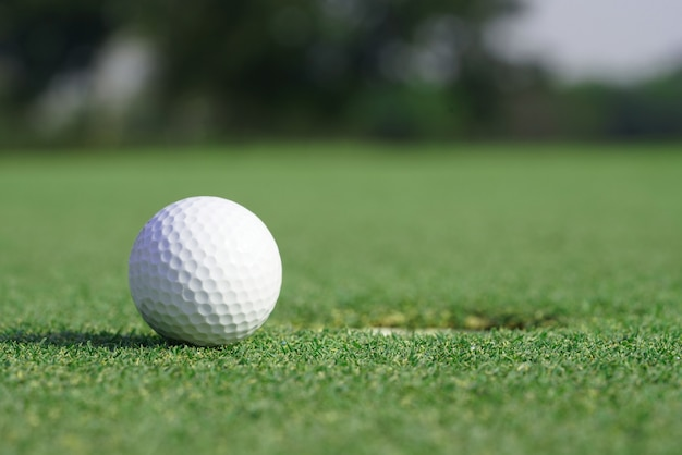 Close-up on a golf ball on a green grass near the hole