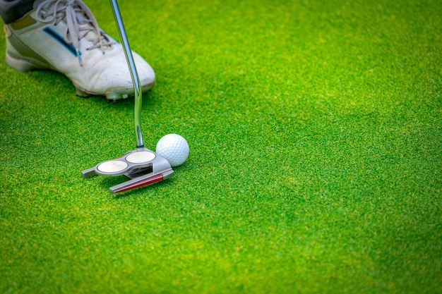 Close up golf club and ball of golfer putting it