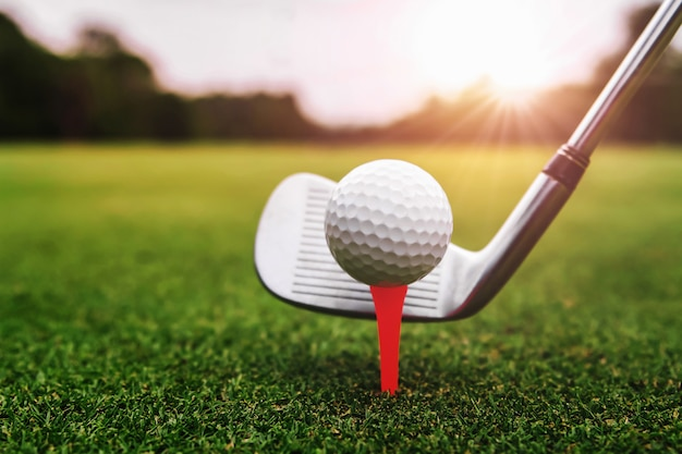 Close up golf club and golf ball on green grass with sunrise background