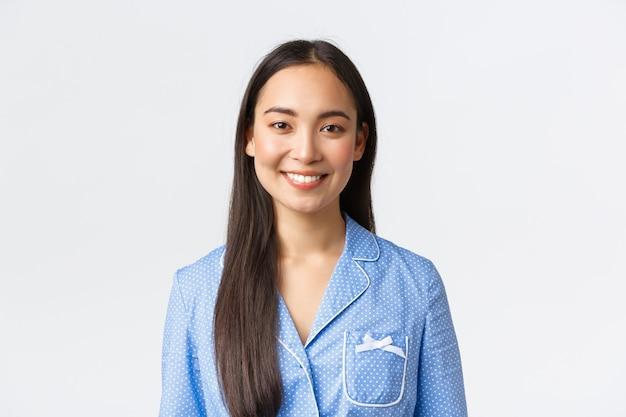 Primo piano di una bella ragazza asiatica in pigiama blu con denti bianchi perfetti, sorridendo alla telecamera felice, svegliandosi al mattino entusiasta, dormendo bene la notte, in piedi sfondo bianco.