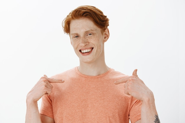 Close-up of good-looking sassy redhead man pointing at himself and smiling
