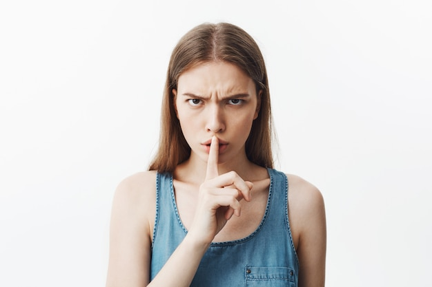 Close up of good-looking young caucasianstudent girl with dark hair in blue shirt holding hand in fromt of lips, making hush gesture with serious and unsitisfied expression. woman tries to calm down l