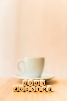 Close-up of good morning cubic blocks with cup of coffee on wooden surface