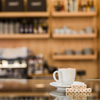 Close-up of good morning wooden blocks with cup of coffee on glass cabinet