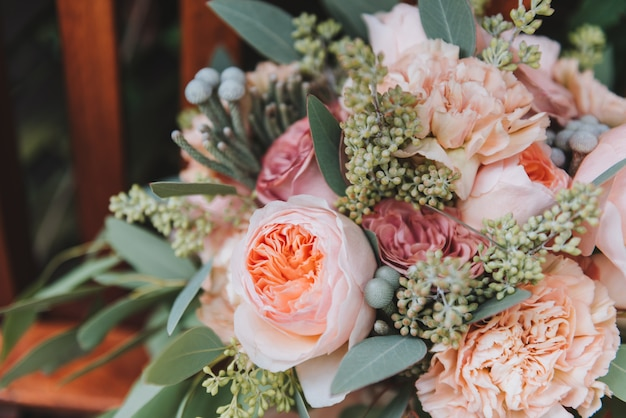 Close up gorgeous wedding bouquet containing eucalyptus and peonies